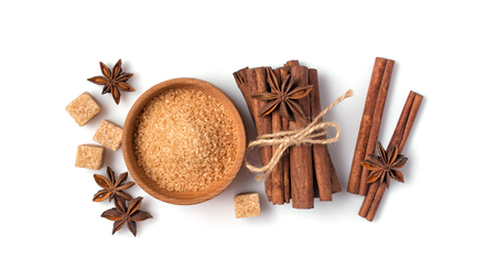 Top view of brown cane granulated and cubes sugar in wooden bowl with spices for confectionery isolated on white background Stock fotó