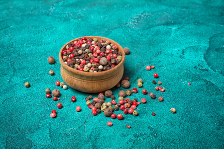 Mixed of peppers in wooden bowl on turquoise concrete background
