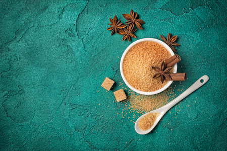 Top view of brown cane granulated and cubes sugar in white bowl with spices for confectionery on green concrete background with copy space Stock Photo