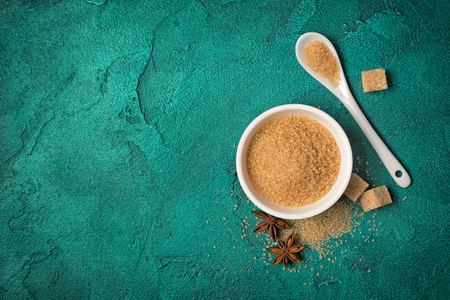 Top view of brown cane granulated sugar in white bowl with spices for confectionery on green concrete background with copy space