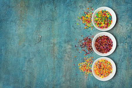 Top view on bright colorful sugar sprinkles or confetti in white bowl as baking decor on blue concrete background with copy space