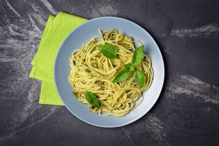 Top view of tasty spaghetti pasta with pesto sauce and basil leaves on black marble background Imagens