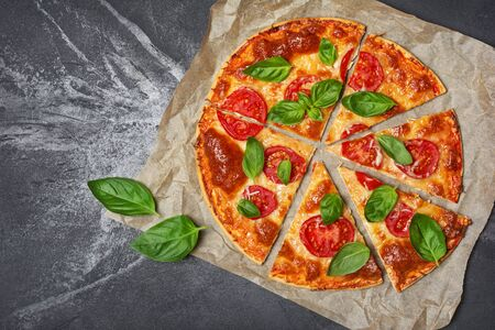 Top view of round pizza margarita with tomato, cheese and basil leaves for vegetarians on black marble background with copy space