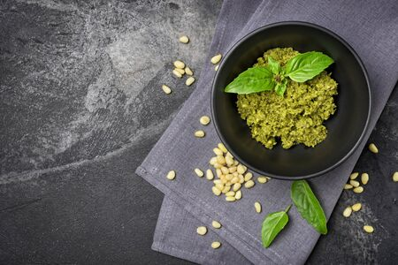 Top view of pesto sauce in bowl with ingredients as pine nuts and basil leaves on black marble background with copy space