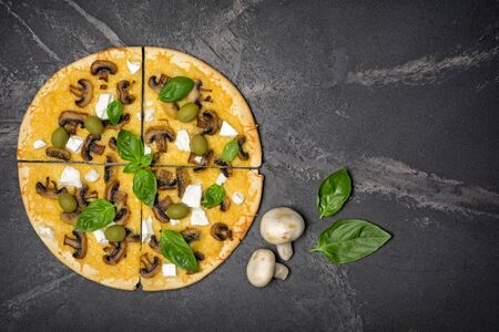 Top view of round pizza with champignons, cheese, olives and basil leaves for vegetarians on black marble background with copy space