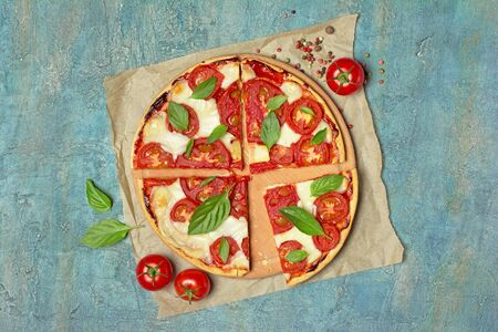 Top view of round pizza margarita with tomato, mozzarella cheese and basil leaves for vegetarians on blue concrete background