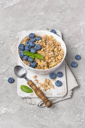 Oatmeal or granola with fresh blueberry in white bowl for healthy breakfast on wooden board and gray concrete background