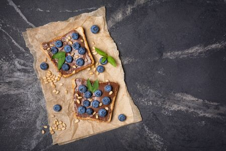 Top view on toast bread with chocolate spread, pine nuts, fresh blueberries and mint for delicious breakfast on black marble background with copy space