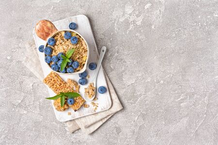 Top view of oatmeal with fresh blueberry in rustic cup and granola energy bar for healthy breakfast on gray concrete background with copy space