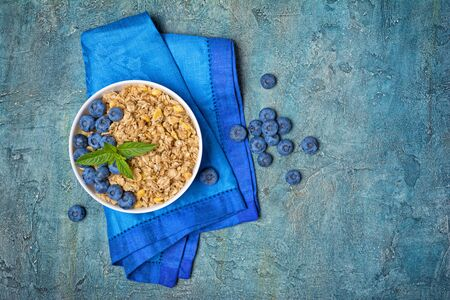 Top view of oatmeal or granola with fresh blueberry in white bowl for healthy breakfast on blue linen cloth and concrete background with copy space