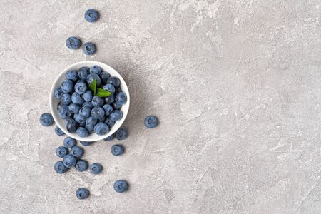 Top view on healthy fresh blueberries in white bowl on gray concrete background with copy space 写真素材