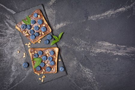 Top view on toast bread with chocolate spread, pine nuts, fresh blueberries and mint for delicious breakfast on black slate board and marble background with copy space