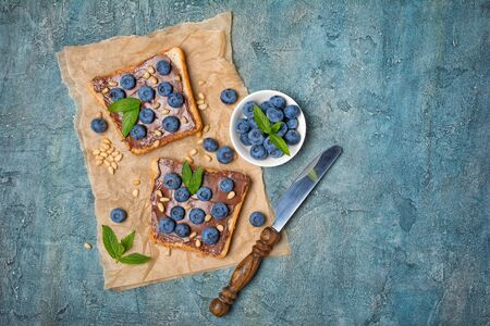 Top view on toast bread with chocolate spread, pine nuts, fresh blueberries and mint for delicious breakfast on blue concrete background with copy space
