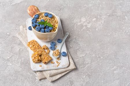 Oatmeal with fresh blueberry in rustic cup and granola energy bar for healthy breakfast on gray concrete background with copy space