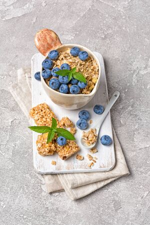 Oatmeal with fresh blueberry in rustic cup and granola energy bar for healthy breakfast on white wooden board and gray concrete background