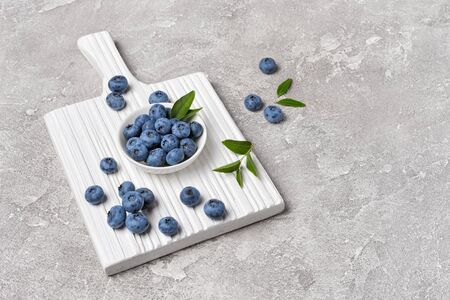 Healthy fresh blueberries in white bowl on wooden board and gray concrete background with copy space