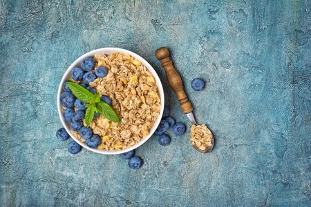 Top view of oatmeal or granola with fresh blueberry in white bowl for healthy breakfast on blue concrete background with copy space 写真素材