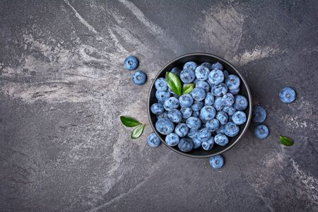 Top view on healthy fresh blueberries in black bowl on marble background with copy space 写真素材
