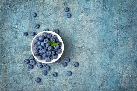 Top view on healthy fresh blueberries in white bowl on blue concrete background with copy space