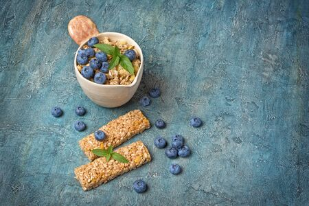 Oatmeal with fresh blueberry in rustic cup and granola energy bar for healthy breakfast on blue concrete background with copy space 写真素材