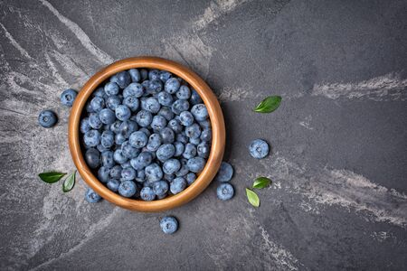 Top view on healthy fresh blueberries in wooden bowl on black marble background with copy space