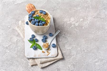 Oatmeal or granola with fresh blueberry in rustic cup for healthy breakfast on wooden board and gray concrete background with copy space 写真素材