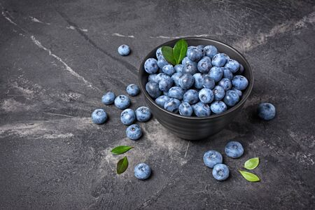 Healthy fresh blueberries in black bowl on marble background with copy space 写真素材