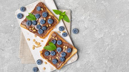 Top view on toast bread with chocolate spread, pine nuts, fresh blueberries and mint for delicious breakfast on gray concrete background with copy space