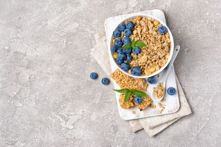 Top view of oatmeal with fresh blueberry in white bowl and granola energy bar for healthy breakfast on gray concrete background with copy space