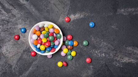 Chocolate multicolored glaze dragee or candies in white bowl on black marble background with copy space