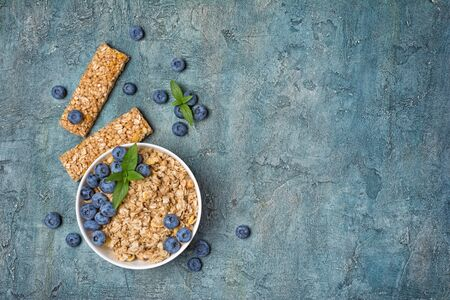 Top view of oatmeal with fresh blueberry in white bowl and granola energy bar for healthy breakfast on blue concrete background with copy space 写真素材