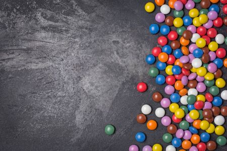 Chocolate multicolored glaze dragee or candies on black marble background with copy space 写真素材