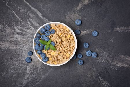 Top view of oatmeal or granola with fresh blueberry in white bowl for healthy breakfast on black marble background with copy space