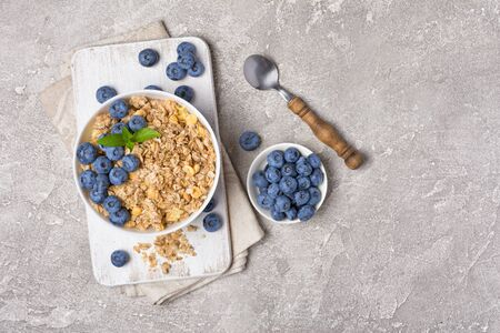 Top view of oatmeal or granola with fresh blueberry in white bowl for healthy breakfast on gray concrete background with copy space 写真素材