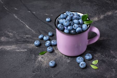 Healthy fresh blueberries in purple mug on black marble background with copy space