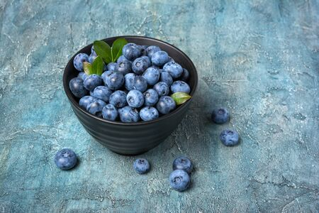 Healthy fresh blueberries in black bowl on blue concrete background with copy space 写真素材