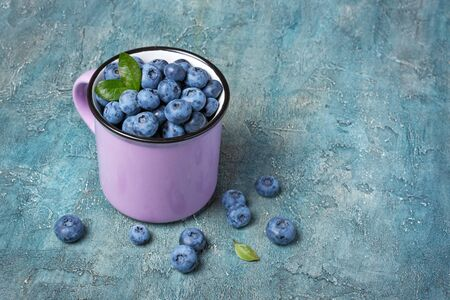 Healthy fresh blueberries in purple mug on blue concrete background with copy space
