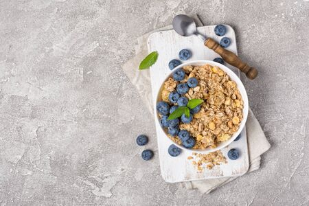 Top view of oatmeal or granola with fresh blueberry in white bowl for healthy breakfast on wooden board and gray concrete background with copy space 写真素材