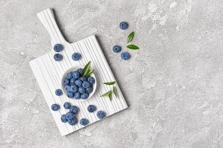Top view on healthy fresh blueberries in white bowl on wooden board and gray concrete background with copy space