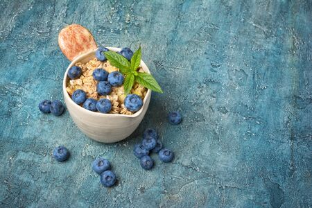Oatmeal or granola with fresh blueberry in rustic cup for healthy breakfast on blue concrete background with copy space 写真素材