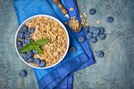 Top view of oatmeal or granola with fresh blueberry in white bowl for healthy breakfast on blue linen cloth and concrete background