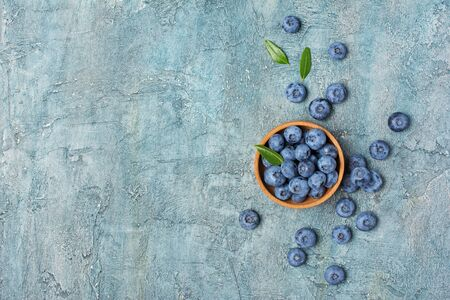Top view on healthy fresh blueberries in wooden bowl on blue concrete background with copy space