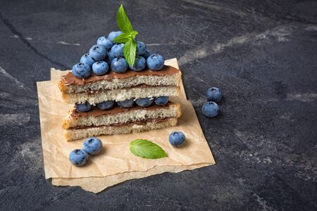 Toast bread with chocolate spread, pine nuts, fresh blueberries and mint for delicious breakfast on black marble background with copy space 写真素材