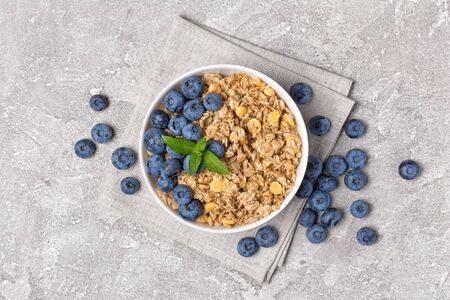Top view of oatmeal or granola with fresh blueberry in white bowl for healthy breakfast on gray concrete background