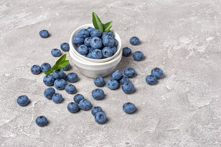 Healthy fresh blueberries in white bowl on gray concrete background with copy space 写真素材