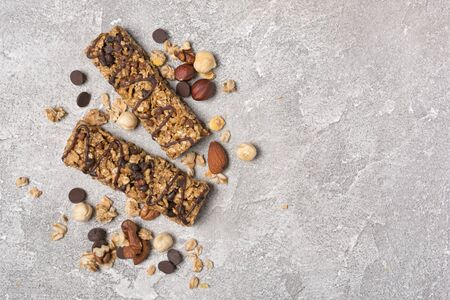 Top view of granola energy bar with mix of nuts for healthy nutrition on gray concrete background with copy space