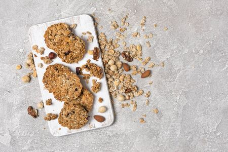Top view of granola with mix of nuts for healthy nutrition on gray concrete background with copy space