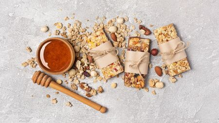 Top view of granola energy bars with mix of nuts and bowl of honey for healthy nutrition on gray concrete background Banco de Imagens