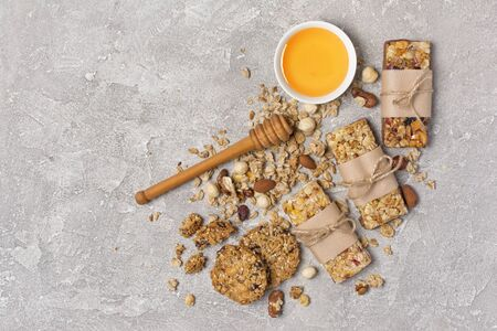 Top view of granola energy bars with mix of nuts and bowl of honey for healthy nutrition on gray concrete background with copy space Banco de Imagens