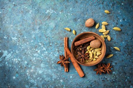 Top view of spices in wooden bowl for mulled wine or masala tea on blue concrete background with copy space